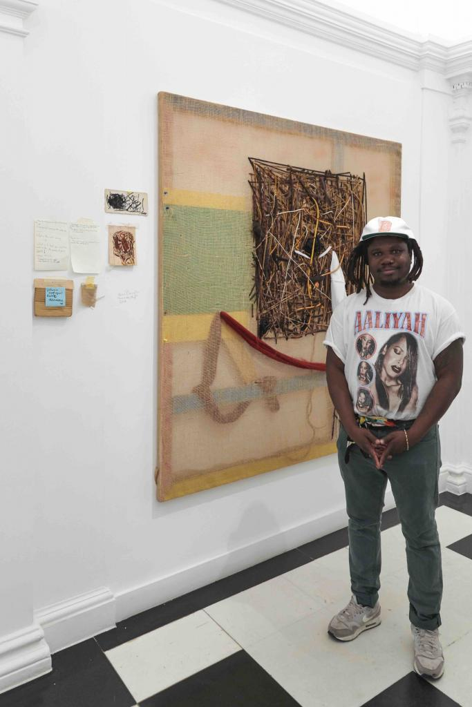 """Artist Alvaro Barrington in front of his artwork, Unc you the plug, 2019 Mixed media on burlap. During the exhibition """"Artists I steal from"""" at Thaddaeus Ropac Gallery © Thaddaeus Ropac Gallery"""