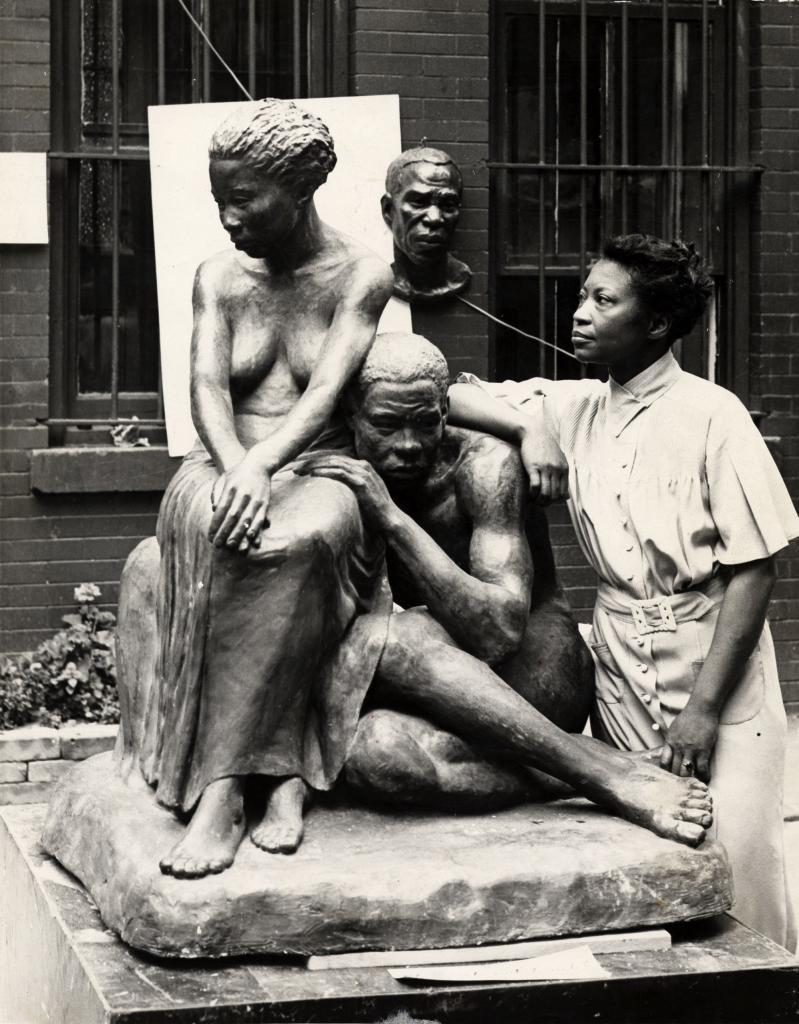 """""""Augusta Savage posing with her sculpture Realization"""", New-York, 1938."""