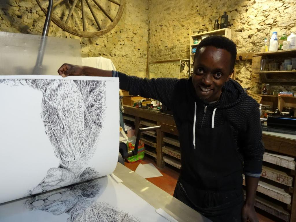Evans Mbugua working on the lithography press. Photo credit Atelier le Grand Village.