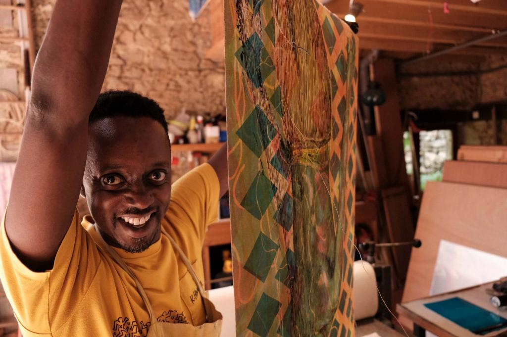 Evans Mbugua holding up a litho-monotype created at Atelier le Grand Village. © Courtesy Atelier le Grand Village.